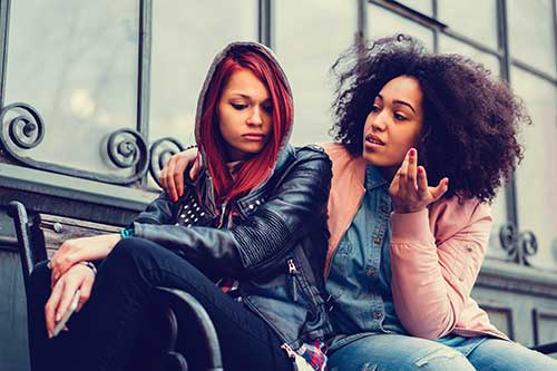 Two multi-ethnic  teen girls sitting on a street bench having a serious discussion.
