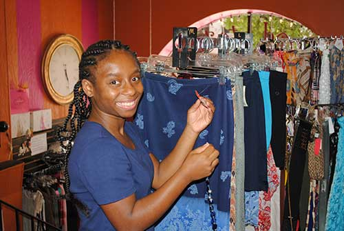 African American teen girl working in a boutique hanging up clothes.