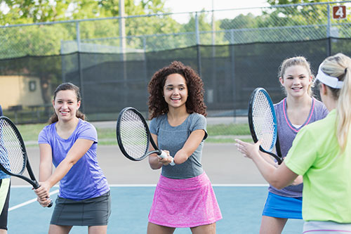 Girl-with-amputated-arm--playing-tennis with peers.