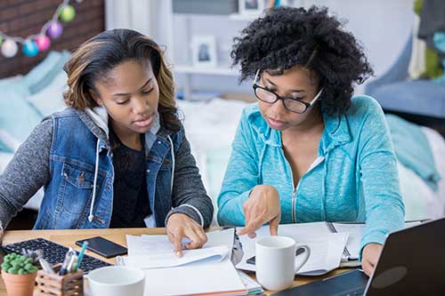 Two teen-girls-writing-on-a-resume-together with papers and a laptop in front of them.