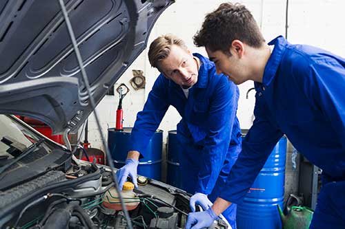 Teen boy working with a mentor on a car engine.