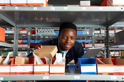 Teen working in warehouse removing product from a shelf.