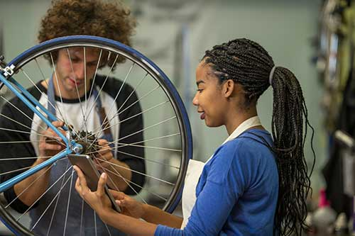 Two teens working on a bicycle in a repair store.
